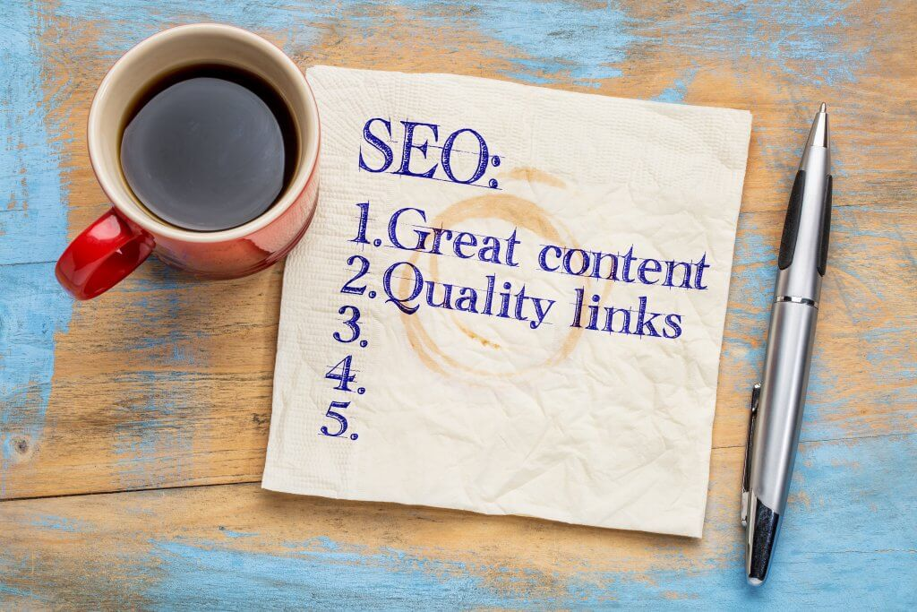SEO (search engine optimization) tips (great content and quality links) on napkin with a cup of coffee